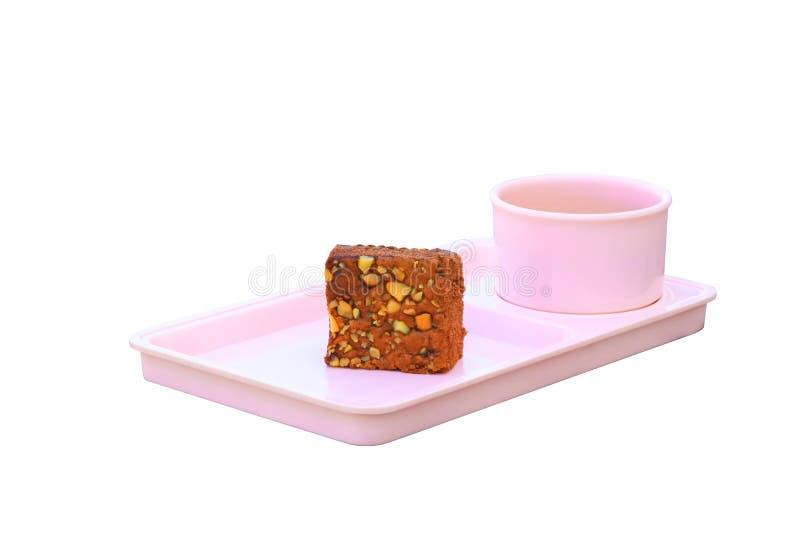 Schokoladenkuchen besprühen mit Nüssen und Kaffeetasse in der rosa Untertasse, die an auf weißem Hintergrund lokalisiert wird stockfoto