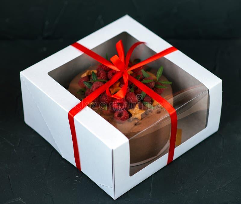 Schokoladenkuchen in einem weißen Kasten mit einem roten Bogen Auf einem schwarzen Hintergrund Inkompetent mit Himbeeren und Keks lizenzfreies stockfoto