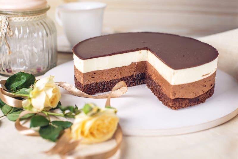 Schokoladenkuchen gemacht von drei unterschiedlichen Schokoladencremeschichten, -WEISS, -milch und -dunkelheit mit Schokolade stockbild