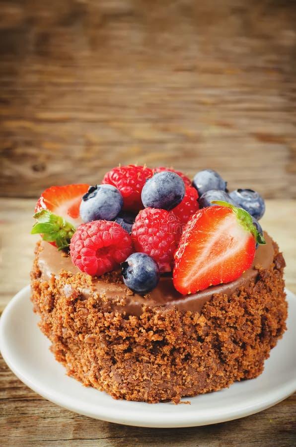 Schokoladenkuchen mit Himbeeren, Blaubeeren und Erdbeeren stockbilder