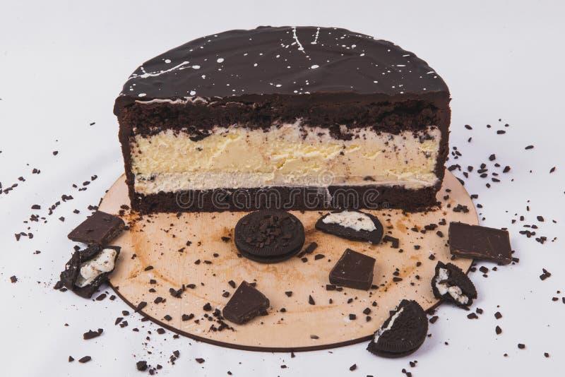 Schokoladenkuchen mit Käsefüllung wird mit Keksen auf einem weißen Hintergrund verziert lizenzfreie stockbilder
