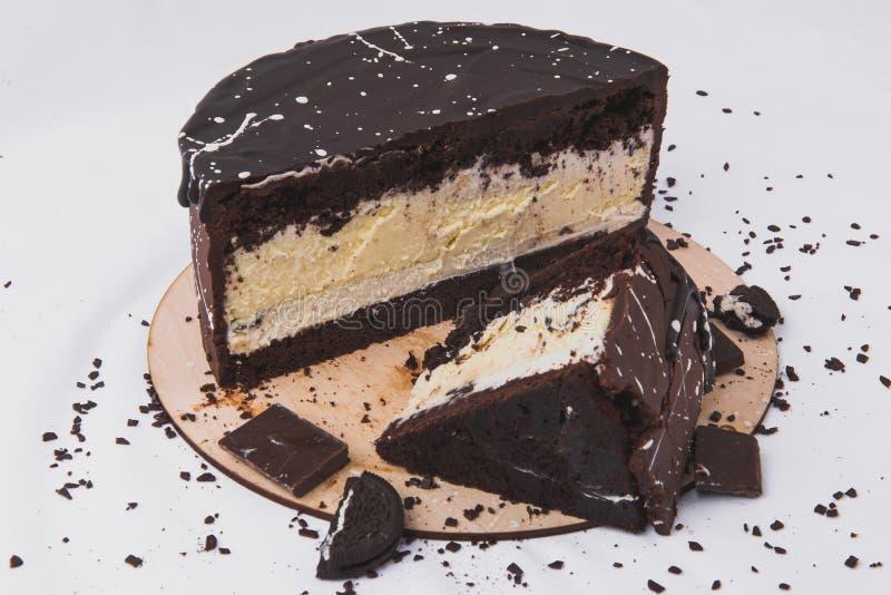 Schokoladenkuchen mit Käsefüllung wird mit Keksen auf einem weißen Hintergrund verziert stockfotos