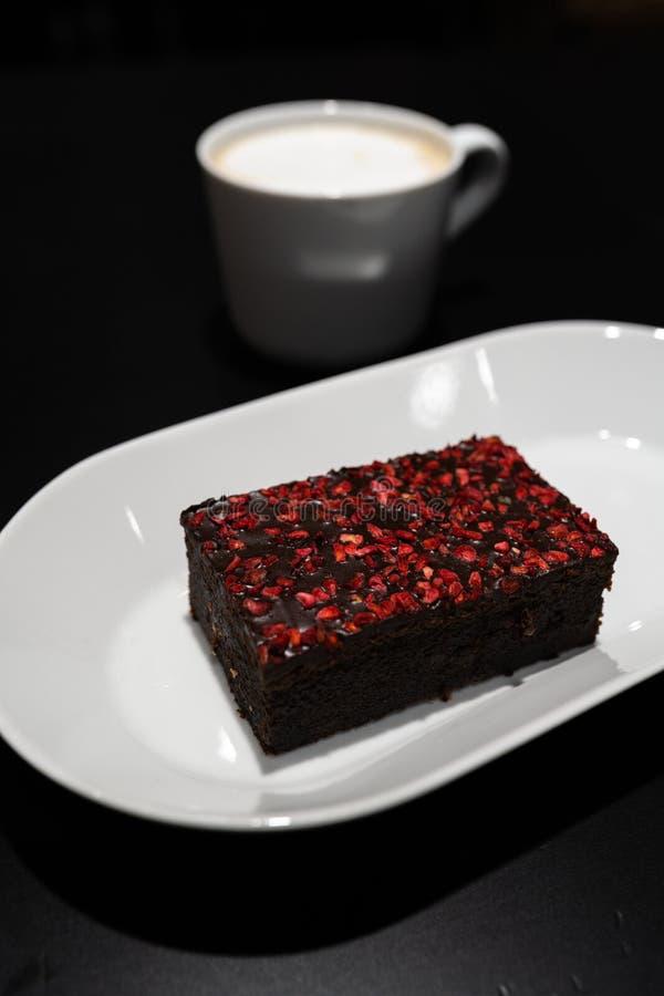 Schokoladenkuchen mit mit klaren roten trockenen Himbeergewürzen mit einer Schale Cappuccinokaffee im Hintergrund lizenzfreies stockfoto