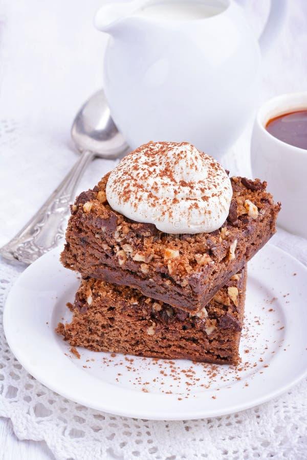 Schokoladenkuchen mit Nüssen und Schlagsahne lizenzfreies stockbild
