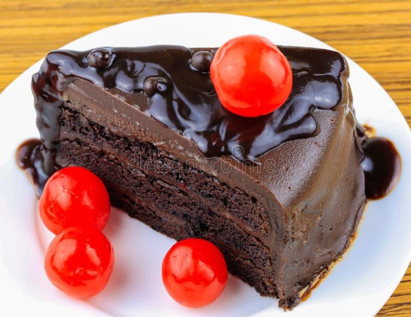 Schokoladenkuchen mit roten Kirschen auf weißer Platte stockbild