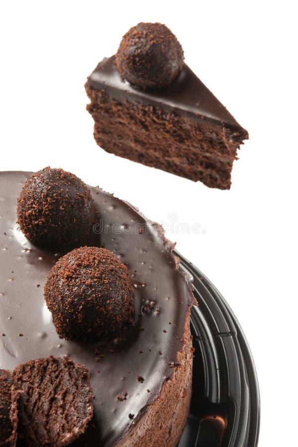 Schokoladenkuchen mit Stück des Kuchens auf Weiß stockbild