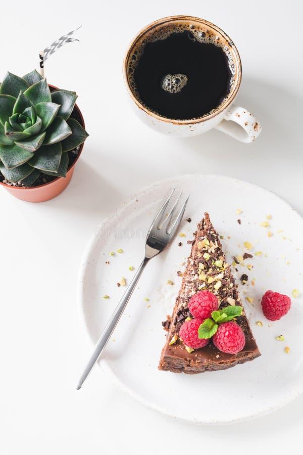 Schokoladenkuchen, Tasse Kaffee und Succulent auf weißer Tabelle stockfotografie