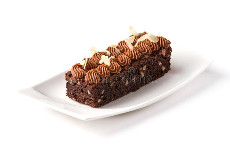 Schokoladenkuchen verziert mit Schokoladencreme- und -mandelflocken in einer weißen Platte auf einem lokalisierten weißen Hinterg lizenzfreies stockfoto