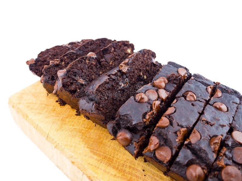 Schokoladenkuchenlaib der roten Bohne mit Schokoladensplitterscheiben auf hölzernem Schneidebrett lizenzfreie stockbilder