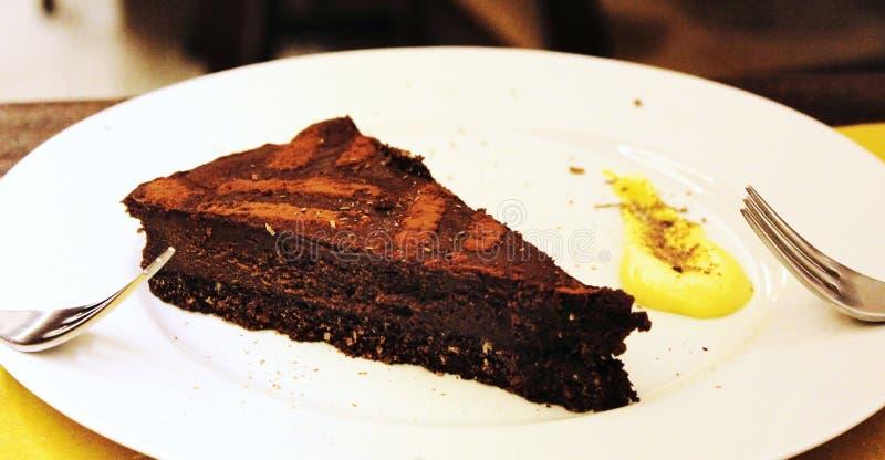 Schokoladenkuchennachtisch auf einer weißen Platte mit zwischen zwei Leuten zu teilen den Gabeln, lizenzfreies stockfoto