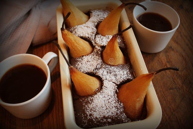 Schokoladenlaibkuchen mit ganzen Birnen backte inner und zwei Schalen Kaffee auf dunklem Hintergrund Beschneidungspfad eingeschlo stockbild