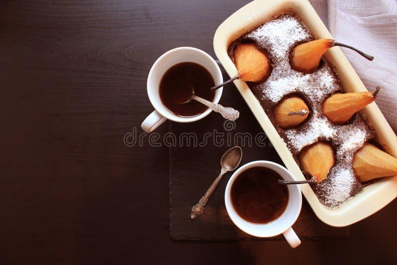 Schokoladenlaibkuchen mit ganzen Birnen backte inner und zwei Schalen Kaffee auf dunklem Hintergrund Beschneidungspfad eingeschlo lizenzfreies stockbild
