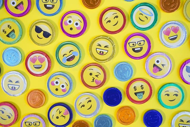 Schokoladenmünzen Draufsichtfoto von Schokoladenmünzen mit verschiedenen Ausdrücken, Pop-Arten-Art, auf einem gelben Hintergrund stockfoto