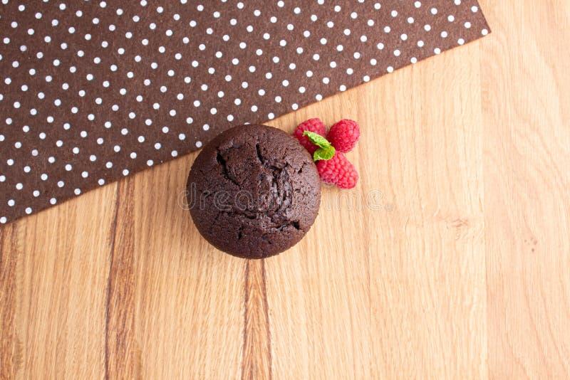 Schokoladenmuffin mit Himbeerbeeren auf einer hellen hölzernen Tabelle lizenzfreies stockbild