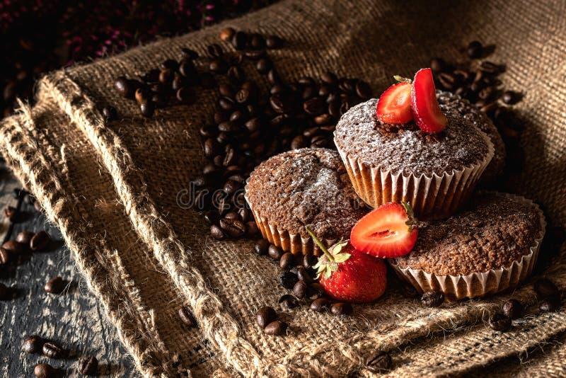 Schokoladenmuffins mit den Erdbeeren besprüht mit Puderzucker auf einer Jutefasertasche lizenzfreies stockfoto