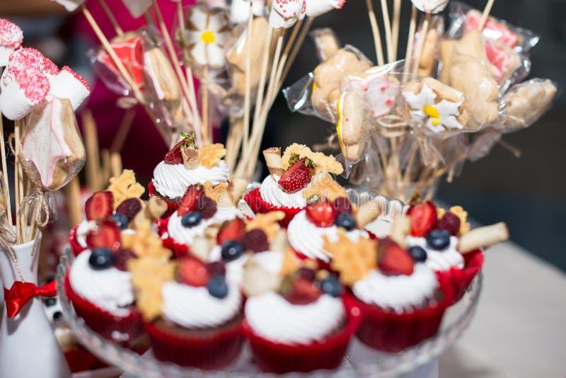 Schokoladenmuffins mit Erdbeeren und weißer Creme auf selektivem Fokus des Holztischs ergebnis stockfoto