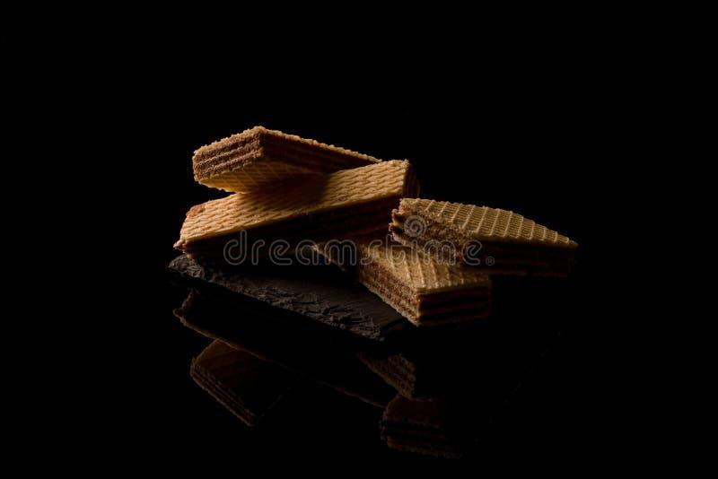 Schokoladenoblaten auf dem schwarzen Hintergrund stockbilder