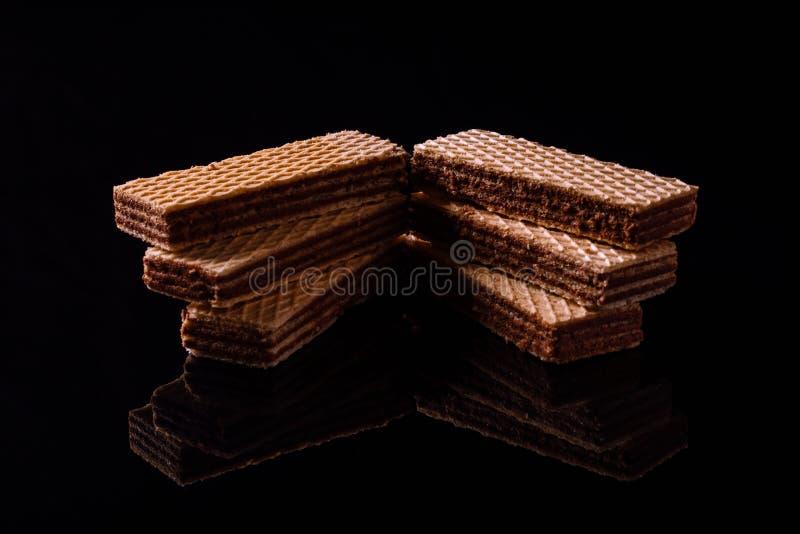 Schokoladenoblaten auf dem schwarzen Hintergrund lizenzfreie stockbilder