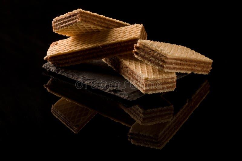 Schokoladenoblaten auf dem schwarzen Hintergrund stockfotos