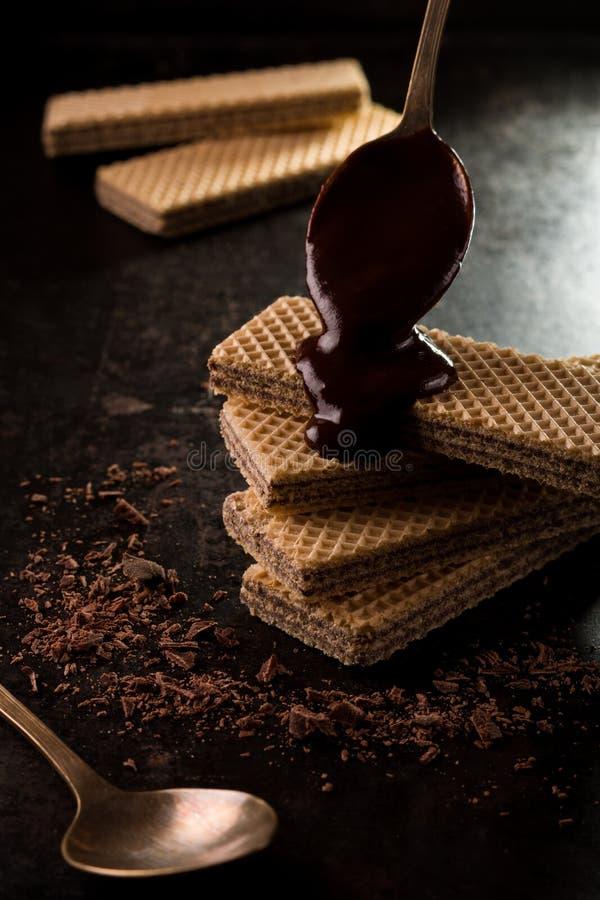 Schokoladenoblaten bedeckt durch eine geschmolzene Schokolade stockfotos
