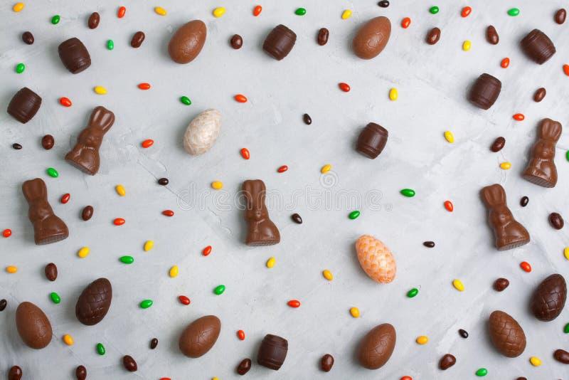 SchokoladenOsterei-, Kaninchen-, Tonne- und Bonbonmuster auf conc lizenzfreie stockfotos