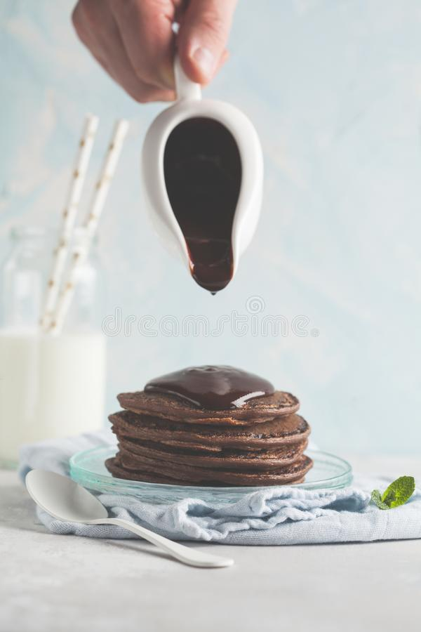 Schokoladenpfannkuchen mit Schokoladensirup, Chef gießt flüssiges choco stockbilder