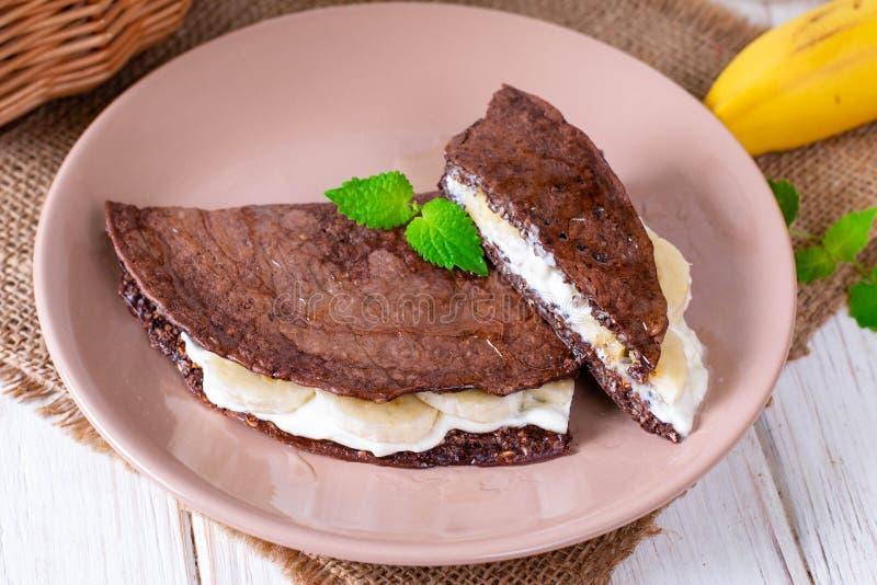 Schokoladenpfannkuchen vom Hafermehl mit Banane und Käse auf einem hölzernen Hintergrund stockbilder
