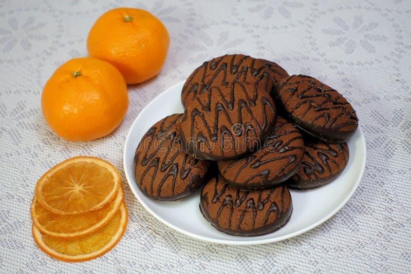 Schokoladenplätzchen auf einer weißen Platte mit getrockneten orange Scheiben und zwei Tangerinen lizenzfreie stockbilder