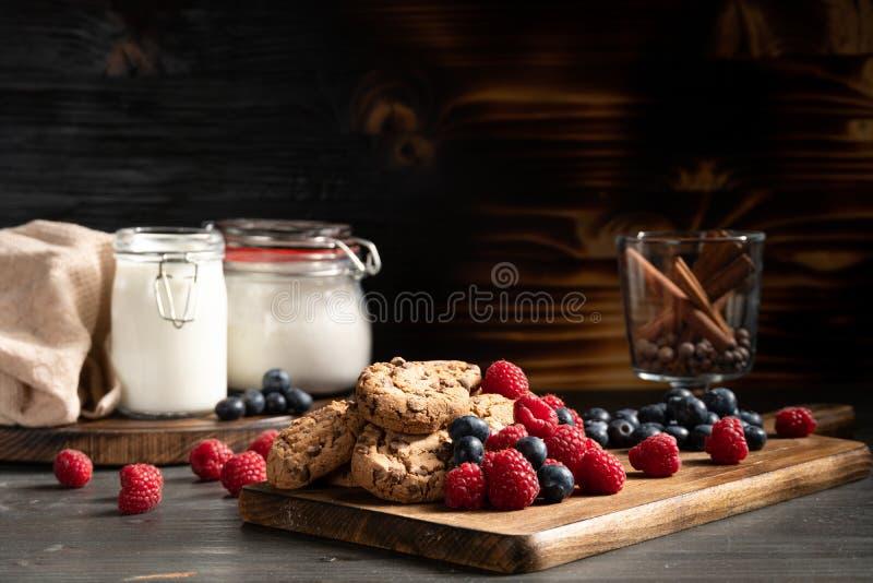 Schokoladenpl?tzchen nahe bei Blaubeeren und rasberry stockfotos