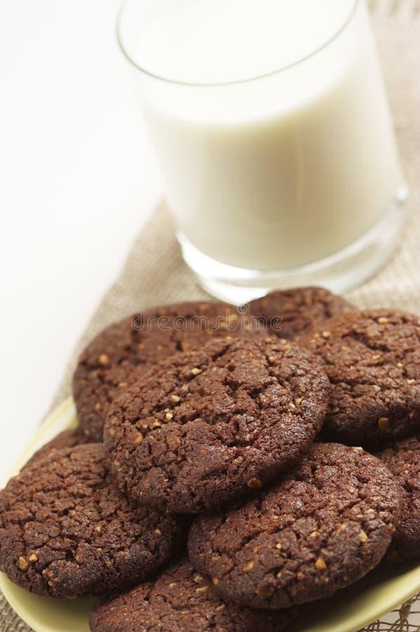 Schokoladenplätzchen und ein Glas Milch stockfotos