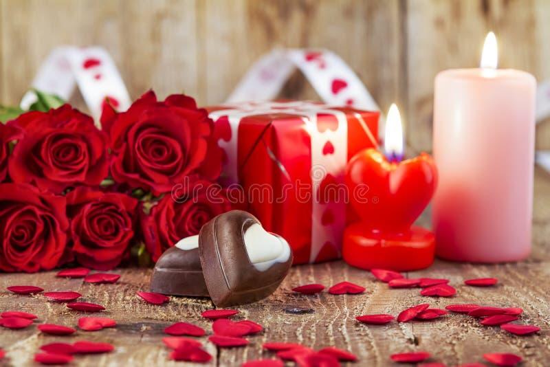 Schokoladenpralinen vor Blumenstrauß von roten Rosen lizenzfreie stockfotos