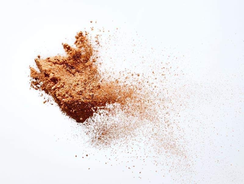 Schokoladenpulverfliegen auf weißem Hintergrund stockbilder
