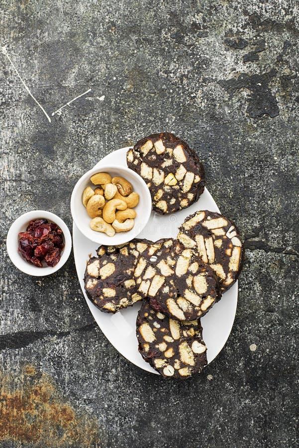 Schokoladensalami mit Nüssen und getrockneten Moosbeeren diente Teil auf einem grauen Schmutzhintergrund mit orange Scheiben und stockfotografie