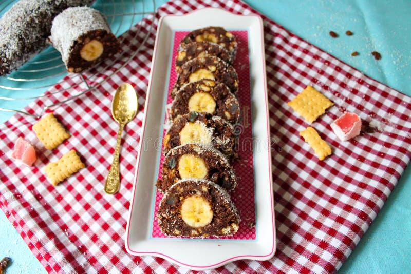 Schokoladensalamirolle mit Bananen- und Kokosnussscheiben stockfoto