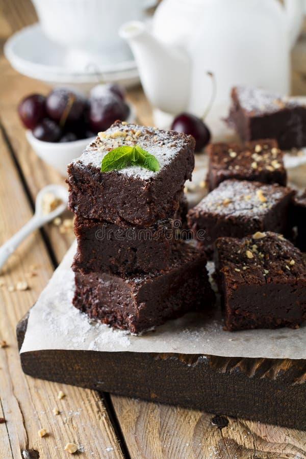 Schokoladenschokoladenkuchen mit Puderzucker und Kirschen auf einem dunklen hölzernen Hintergrund lizenzfreie stockfotos