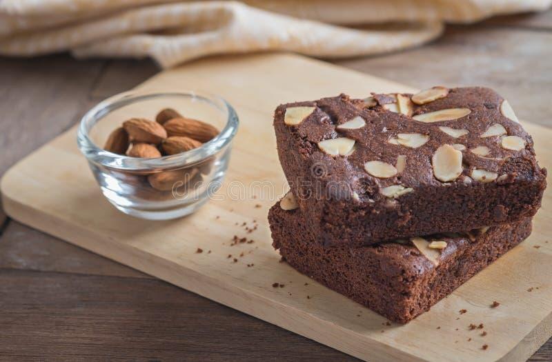 Schokoladenschokoladenkuchenbelag mit Mandelscheiben auf hölzerner Platte lizenzfreies stockfoto