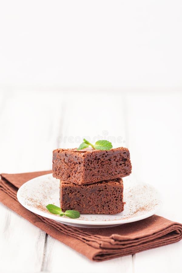 Schokoladenschokoladenkuchenquadrat bessert im Stapel auf der weißen Platte aus, die mit tadellosen Blättern und Kakaopulver auf  lizenzfreie stockfotografie