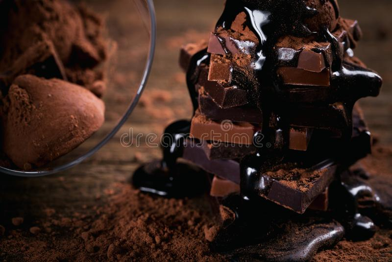 Schokoladensirupbratenfett auf Stapel der Dunkelheit und des Milchschokoladestapels, Trüffeln lizenzfreie stockfotografie