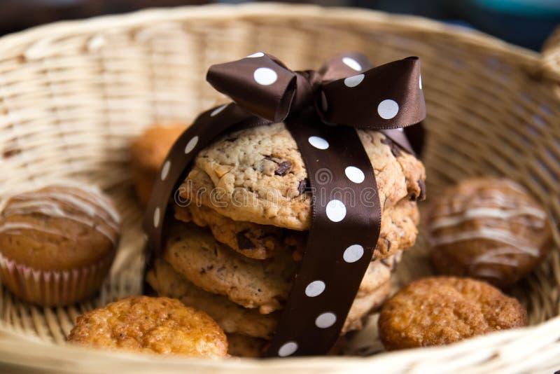 Schokoladensplitterplätzchen in einem Korb mit braunem silk Bogen mit weißen Punkten lizenzfreie stockfotos