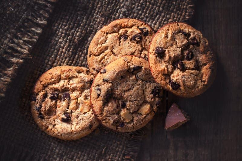 Schokoladensplitterplätzchen, frisch gebacken auf rustikalem Holztisch S stockbild