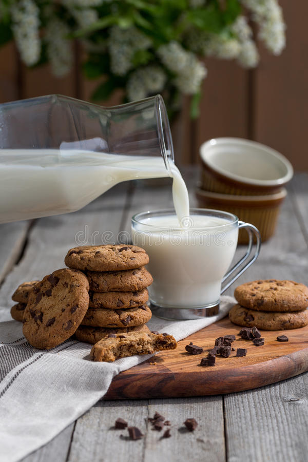 Schokoladensplitterplätzchen mit Milch auf altem rustikalem Holztisch stockbild