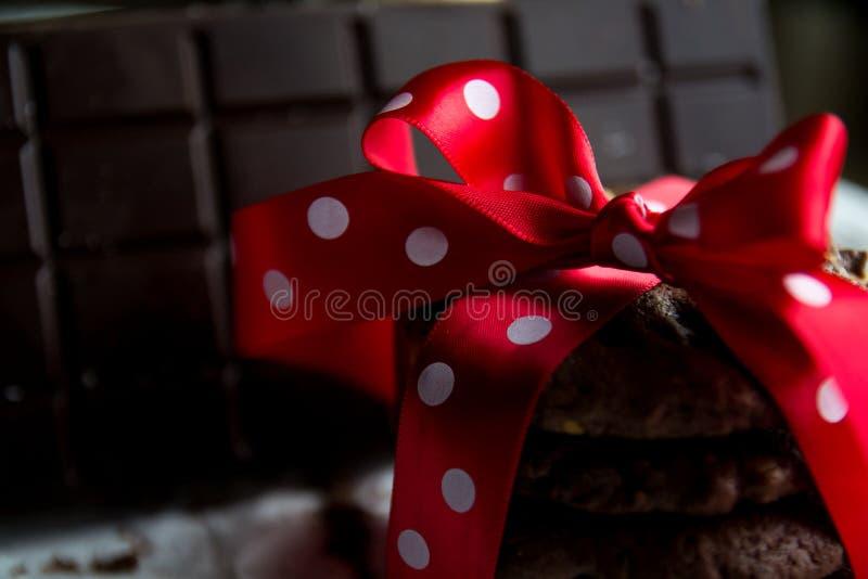 Schokoladensplitterplätzchen mit Schokoriegel und roter silk Bogen mit weißen Punkten lizenzfreie stockfotos
