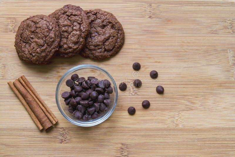 Schokoladensplitterschokoladenkuchenplätzchen mit dem Zimt angezeigt auf einem hölzernen Schneidebrett lizenzfreies stockbild
