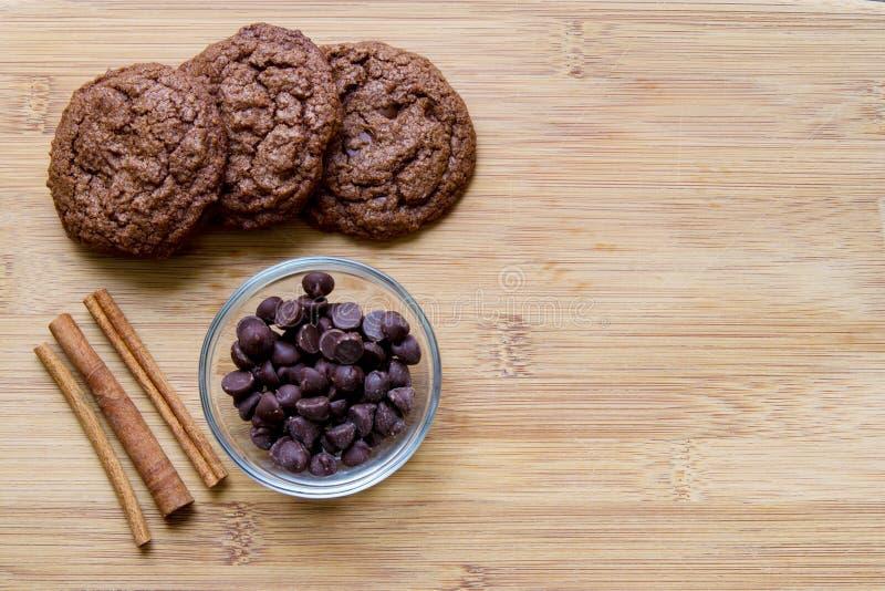 Schokoladensplitterschokoladenkuchenplätzchen mit dem Zimt angezeigt auf einem hölzernen Schneidebrett lizenzfreie stockfotografie