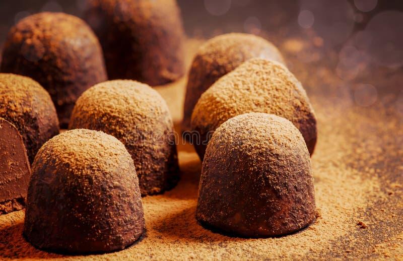 Schokoladentrüffeln mit Kakaopulver auf dunkler Tabelle, selektiver Fokus lizenzfreie stockbilder