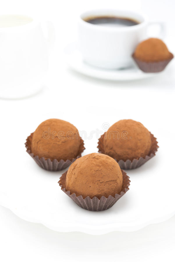 Schokoladentrüffeln und ein Tasse Kaffee auf einem weißen Hintergrund stockbilder