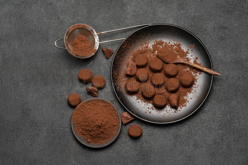 Schokoladentrüffelsüßigkeiten und Kakaopulver auf dunklem konkretem Hintergrund stockbilder