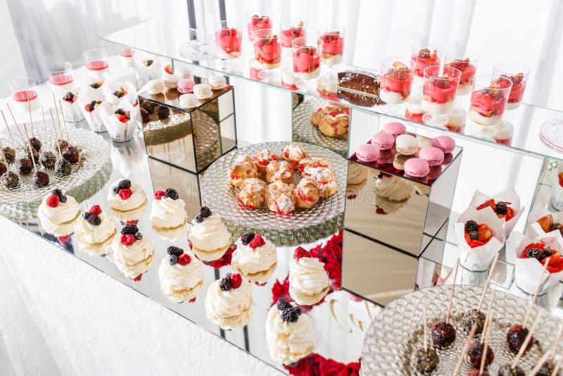 Schokoriegel mit vielen Nachtischen, Meringe, kleinen Kuchen, Frucht und Bonbon backt zusammen Süße Tabelle für Geburtstag oder H lizenzfreies stockbild