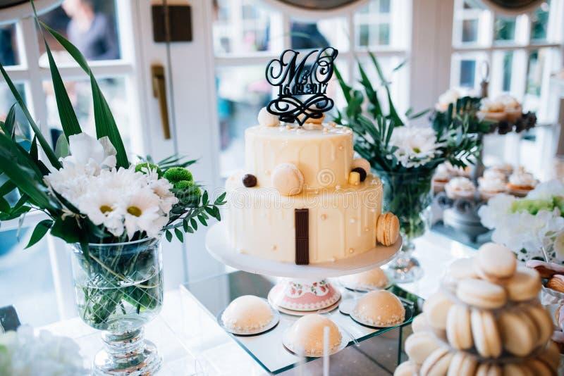 Schokoriegel und Hochzeitstorte mit Blumen Tabelle mit Bonbons, Buffet mit kleinen Kuchen, Süßigkeiten, Nachtisch stockfotografie