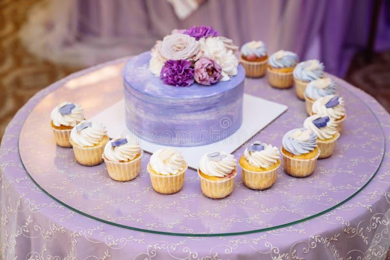 Schokoriegel und Hochzeitstorte Tabelle mit Bonbons, Buffet mit kleinen Kuchen, S??igkeiten, Nachtisch stockbild